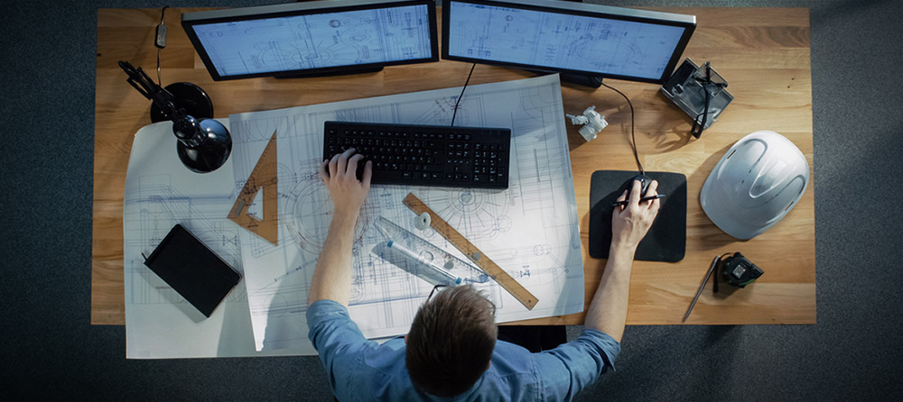 top view of construction manager on desk with blueprints