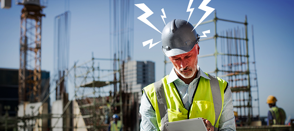 construction manager at a construction site looks angry looking at his iPad
