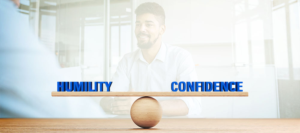 the words Humility and Confidence are balanced over a wooden sphere scale